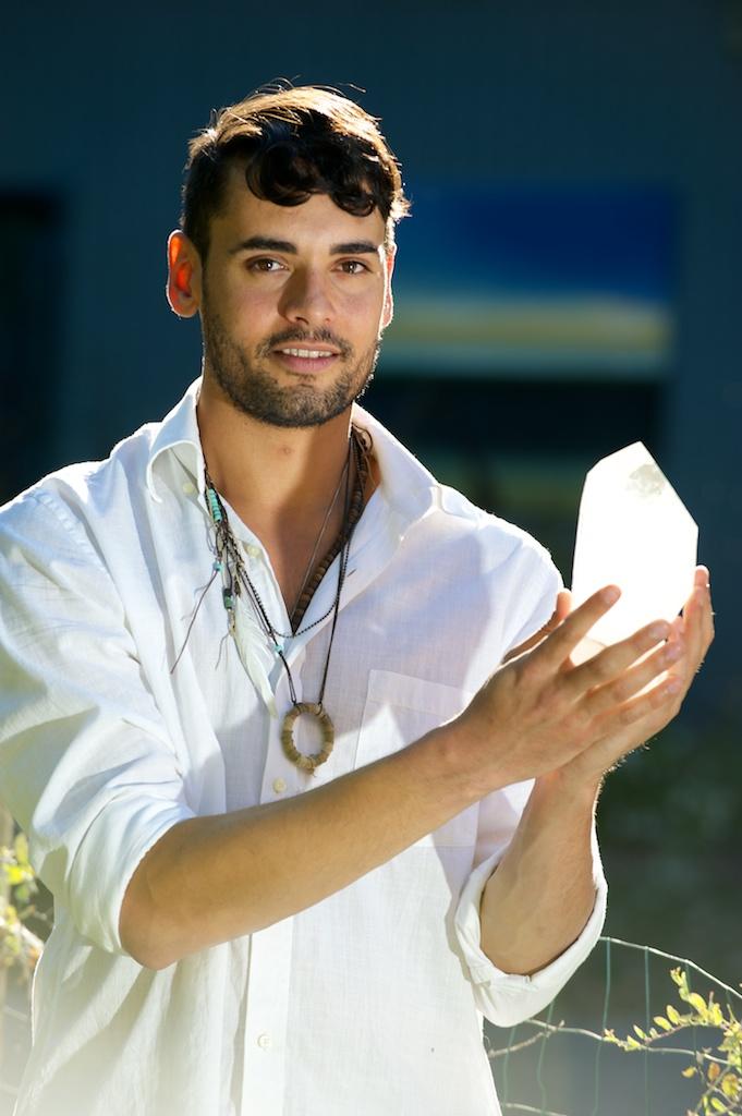John Corsa, crystal healer, holding clear Quartz crystal